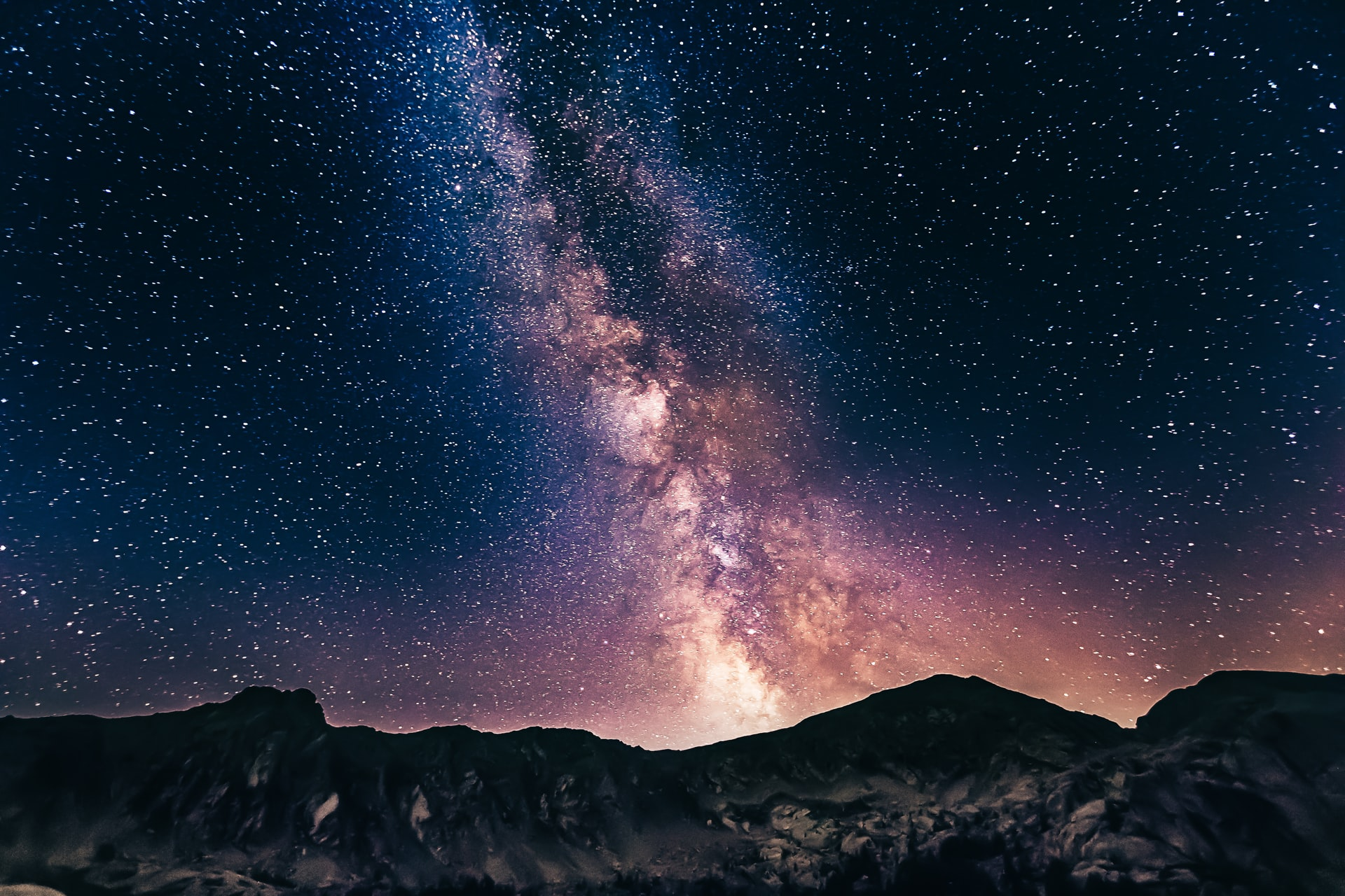 picture of the milky way rising over hills
