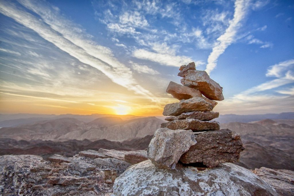 picture of inukshuk in a sunset overlooking a valley and mountains